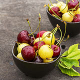 Red and yellow cherries in dark ceramic bowls on a dark background. Top view Stock Image