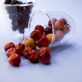 Red and yellow cherries spilled from the glass Stock Photos