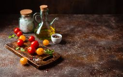 Red and yellow fresh tomatos, basil and olive oil stock photography