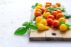 Red and yellow cherry tomatoes on a cutting board with basil lea Royalty Free Stock Photo
