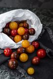 Red and yellow cherry tomatoes on a dark marble table. royalty free stock image