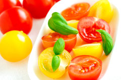 Red and yellow cherry tomatoes in plate on white tablecloth clos Royalty Free Stock Photo