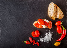Red and yellow cherry tomatoes on slate with sliced bread, brusc Stock Photos