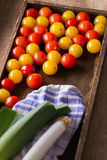 Red and yellow cherry tomatoes in wooden box Stock Photo