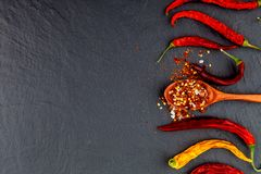 Red and yellow chili pepper dried. On a stone black background. royalty free stock photo