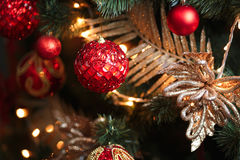 Red and yellow christmas tree decorations. Red baubles hanging from a decorated Christmas tree Royalty Free Stock Photos