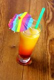 Red, yellow cocktail with lemon, straw and umbrella deco Royalty Free Stock Photos