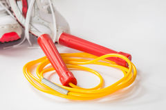 Red and yellow color jump rope with sport shoe Stock Photo
