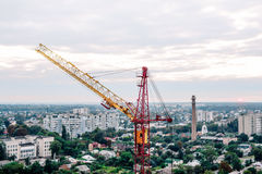 Red yellow construction tower crane against sky. Horizon, evening skyline. Building and construction. Machinery and equipment.  Stock Images