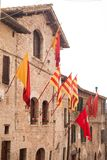 Narrow street with flags in Assisi town in Umbria region stock photography