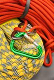 Red and yellow dynamic ropes and attached carabiner. Royalty Free Stock Photos