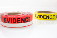 Red and yellow evidence tape on white background. Focus on back object stock images