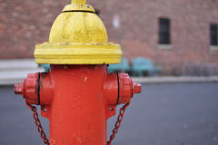 Red and yellow fire hydrant with brick background Royalty Free Stock Photo