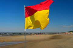 Red and yellow flag on the beach of the Baltic Sea. Fluttering in the wind on the horizon with holiday travelers Royalty Free Stock Image