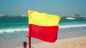Red yellow flag. Beach Dubai Marina. Sunny day at the sea. Red yellow flag. Beach Dubai Marina. Sunny day at the sea stock video footage