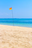 Red and yellow flag pole at he beach Royalty Free Stock Image