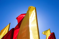 Red and yellow flags fluttering in the wind Royalty Free Stock Image