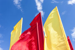 Red and yellow flags fluttering in the wind Royalty Free Stock Photos