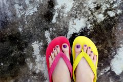 Red and Yellow Flip Flops. Selfie Woman Wearing Flip Flop Standing on Cement Background Royalty Free Stock Photos
