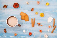 Red and yellow flowers, ginger biscuits and a cup of coffee on a blue wooden background. Texture and background. Concept stock images