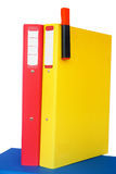 Red and yellow folders on a blue one Stock Photos