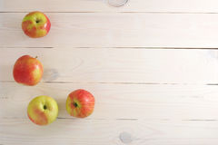 Red yellow fresh apples on wooden white background Royalty Free Stock Images