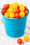 Red and yellow fresh cherry tomatoes with water drops in bowl Stock Image