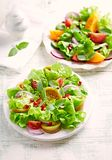 Red and yellow fresh tomato salad with pomegranate seeds stock photo