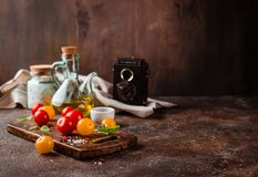Red and yellow fresh tomatos, basil and olive oil stock photos