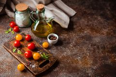 Red and yellow fresh tomatos, basil and olive oil stock images