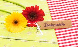Two gerbera flowers and greeting card with german word, Dankeschoen, means thanks. Red and yellow gerbera flowers with card with german word, Dankeschoen, means royalty free stock photos