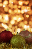 Red,yellow and gold Cristmas Baubles. Red,yellow and gold Christmas baubles on background of defocused golden lights and sparkles Stock Image