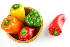 Red yellow and green bell pepper in a wooden bowl over white. Background Stock Image