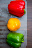 Red, Yellow and Green Bell Peppers on the Chopping Board, Dark B Royalty Free Stock Photo