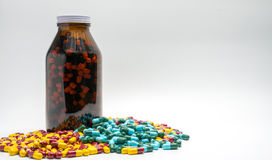Red, yellow, green, blue antibiotic capsule pills and amber bottle, drug resistance. Copy space Stock Photography