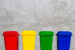 Red, Yellow, Green and Blue Recycle Bins. Concrete wall background.