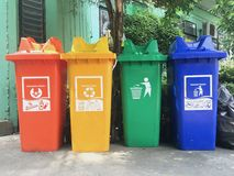 Red yellow green and blue, recycle bins with recycle free text space and symbol near building outdoor. royalty free stock image