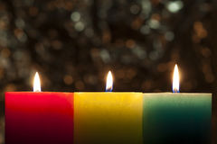 Red, yellow and green colourful candles with blurred bokeh backg Stock Image