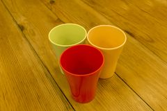 Red yellow green empty plastic cup close-up stand on the wooden surface of the table royalty free stock photos