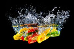 Red yellow and green pepper slices fall into water, on black background Stock Images