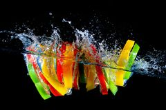 Red yellow and green pepper slices fall into water, on black background Stock Photos