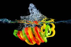 Red yellow and green pepper slices fall into water, on black background Stock Photography