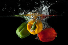 Red, Yellow, Green Pepper Splash. Red, yellow and green pepper drop in a water tank creating a splash Royalty Free Stock Photo