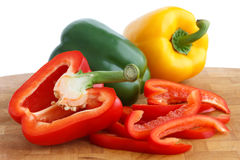 Red, yellow and green peppers on chopping board Stock Image