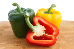 Red, yellow and green peppers on chopping board Stock Photography