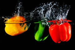 Red yellow and green peppers fall into water Royalty Free Stock Photos