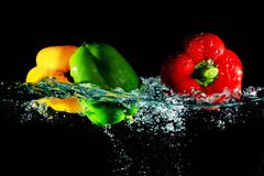 Red yellow and green peppers fall into water Stock Photo