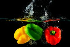 Red yellow and green peppers fall into water Royalty Free Stock Image