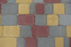 Red, yellow, grey concrete pavement blocks. From above Stock Image