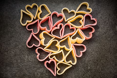 Red and yellow heart shaped pasta in shape of heart, top view, f Royalty Free Stock Image
